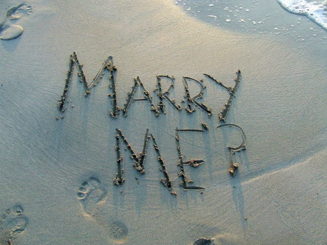 The word 'marry me' written on the sandy beach